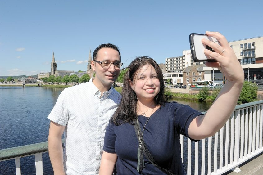Texan visitors to Inverness, Veronica Garcia and Daniel Luke photograph themselves on the Ness Bridge in Inverness. Photo by Sandy McCook