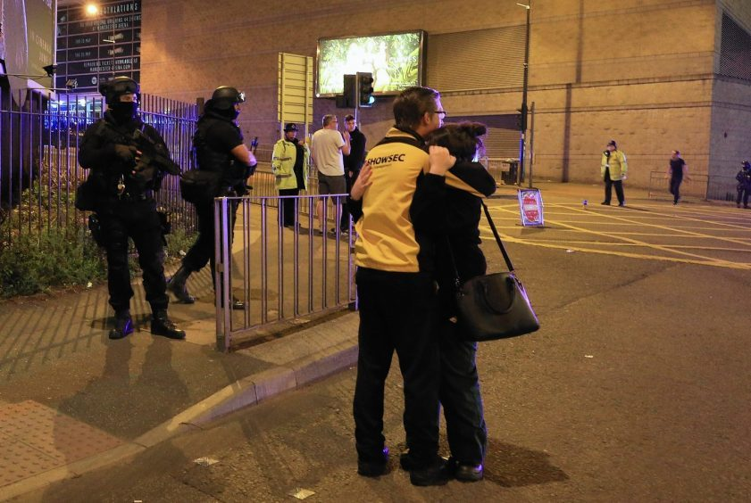 Armed police (left) at Manchester Arena after reports of an explosion at the venue during an Ariana Grande gig