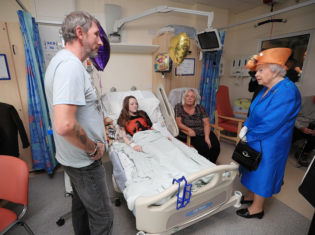 Queen Elizabeth II speaks to Millie Robson, 15, from Co Durham, and her mother, Marie and Father David during a visit to the Royal Manchester Children's Hospita