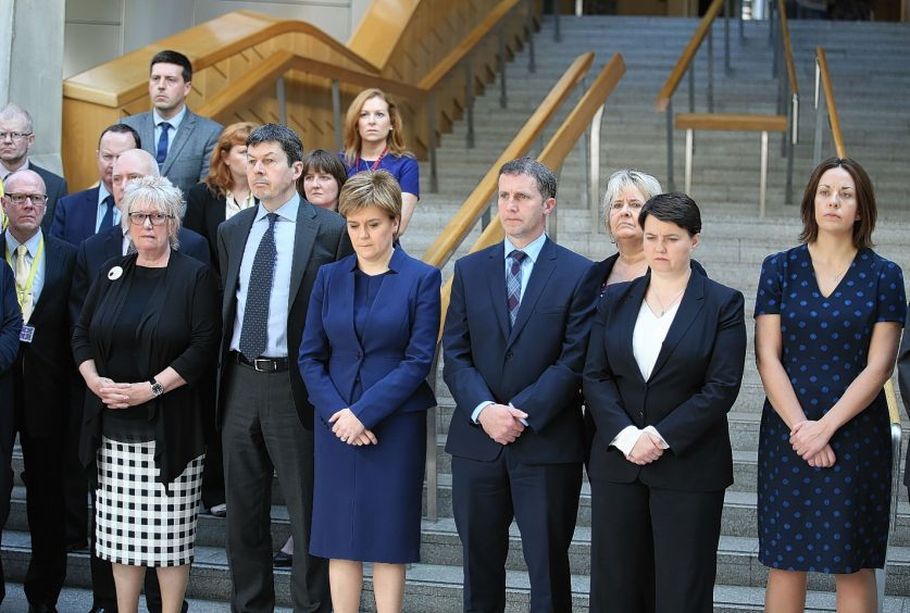 First Minister Nicola Sturgeon joins colleagues in observing a minute's silence in the Garden Lobby of the Scottish Parliament
