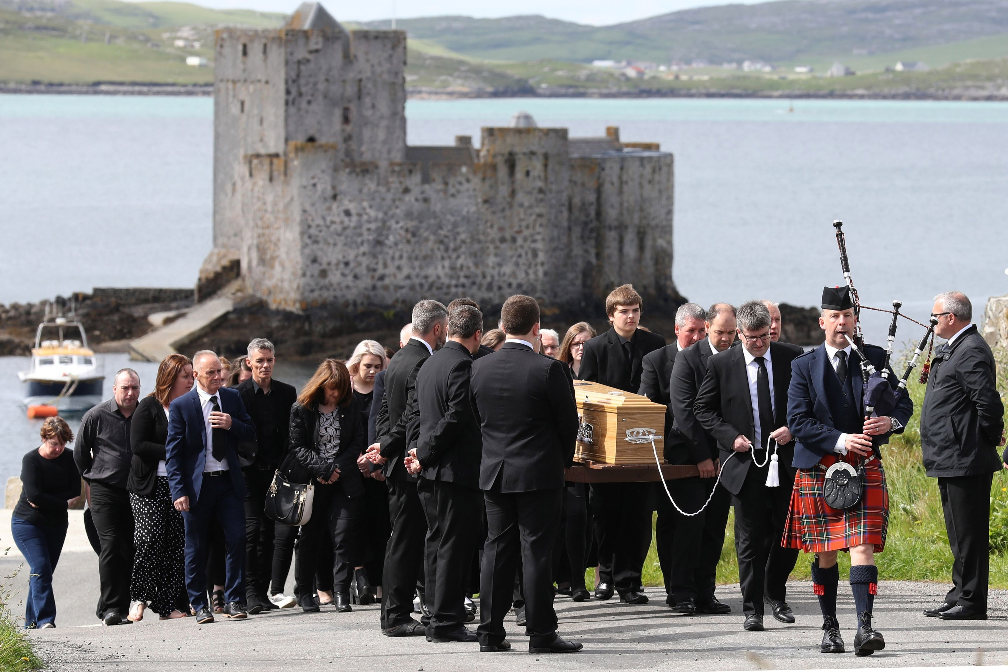 BARRA, UNITED KINGDOM - JUNE 5:  Roddy MacLeod, Eilidh's father leads the funeral procession as it passes Kisimul Castle on its way to the Church of Our Lady, Star of the Sea, in Castlebay on Barra