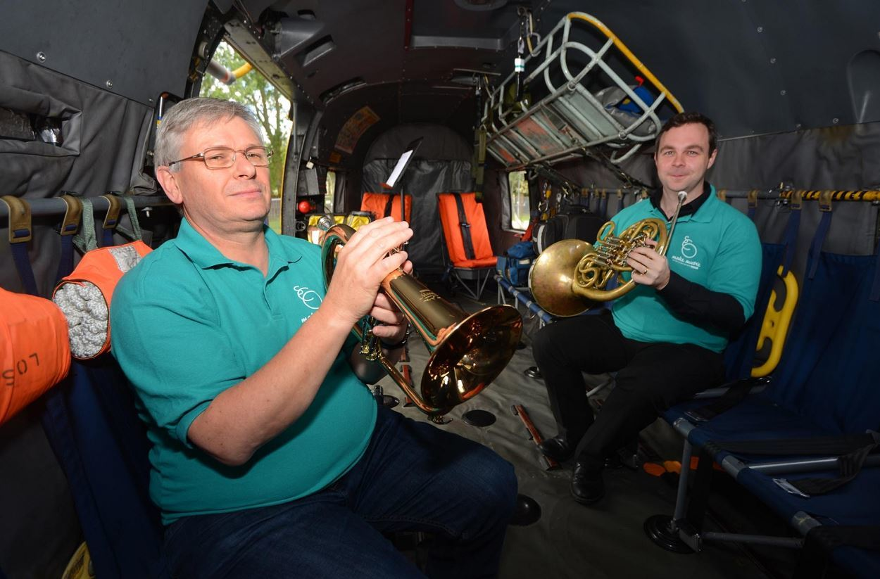 Orchestra members Peter Franks and Patrick Broderick performing on board the Sea King helicopter.