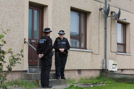 Two police officers stand guard outside a house at in Willowbank, Wick