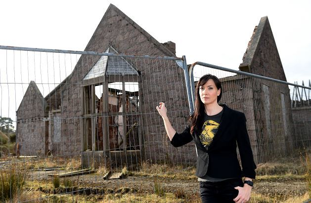 Resident Carrie Zeiler stands in front one of the derelict buildings on the site of Kingseat hospital.