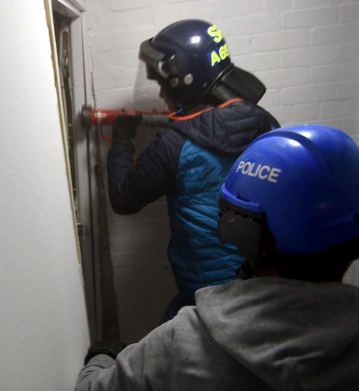 Officers ram through the door of the flat in Regent Court, Aberdeen.