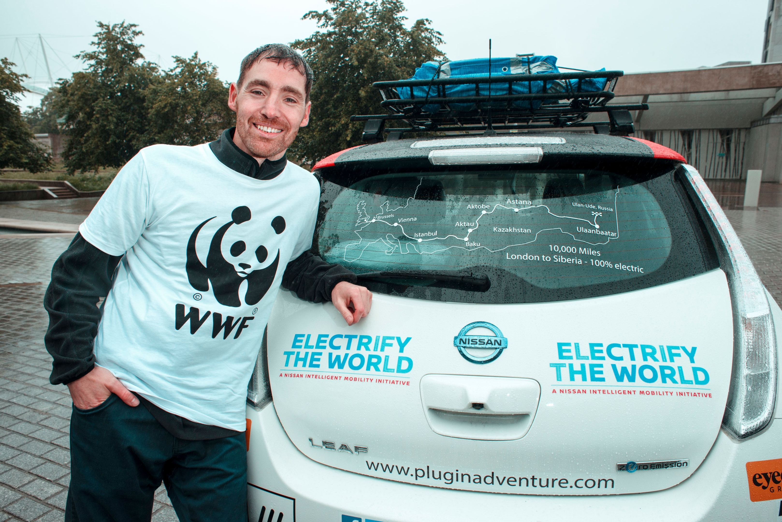 Chris Ramsey next to his Nissan Leaf