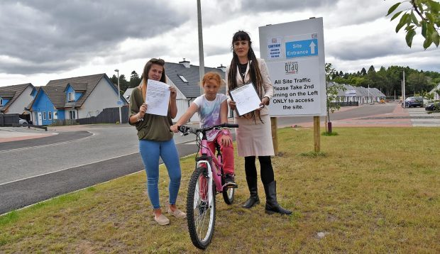 Chloe Hardy Kiltarlity Petition Chloe Hardy (right) with Laura Thompson and Chloe Thompson (8) and their petition. Pic - Phil Downie