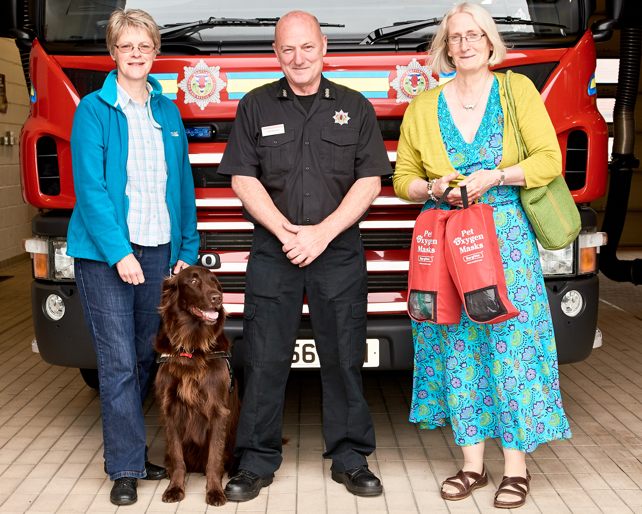 Left to right: Pheona Horne with Loki the dog, Lerwick station manager, Graham Reid and Tricia Brown holding two of the life-saving kits.