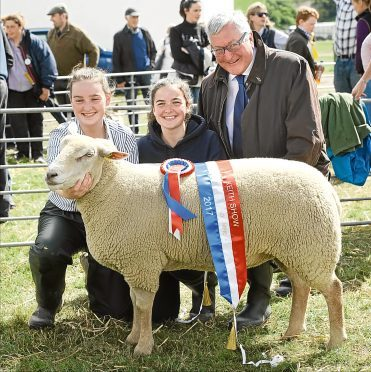 Rural Economy Secretary Fergus Ewing presents Erin and Eilidh Duncan with the sheep interbreed championship rosette.