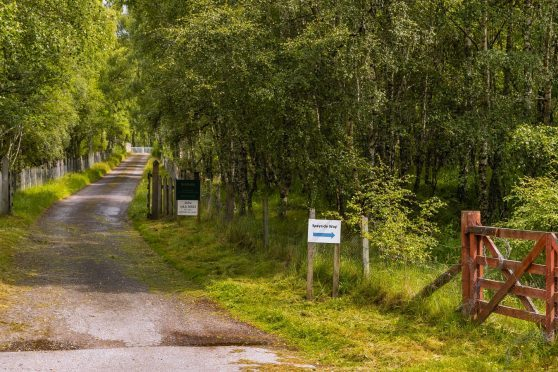 The entrance to Kinrara Estate from adjacent to Dalraddy Holiday Park, with a sign directing away from the ropad to the Speyside Way gate.