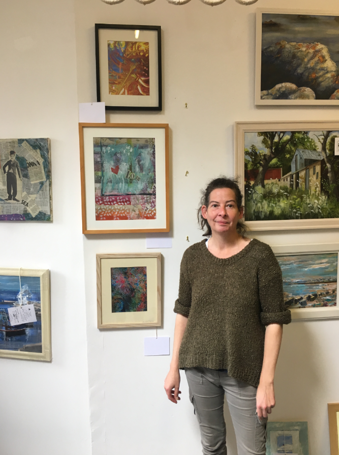 Artist Mandy Middler stands in front of some her work