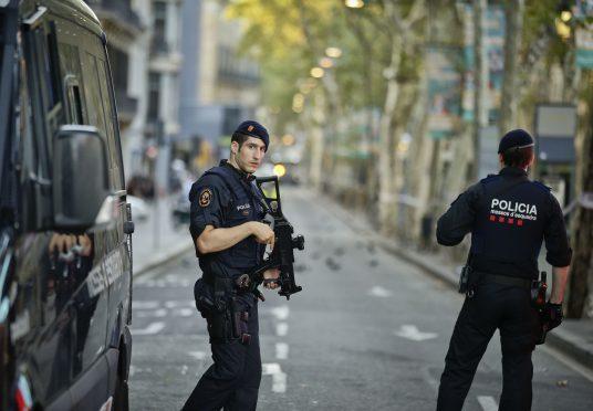 Armed police officers patrol a deserted street in Las Ramblas, in Barcelona, Spain