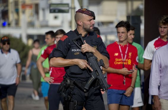 An armed policeman grimaces while on patrol in Cambrils, Spain, Friday, Aug. 18, 2017. Spanish police on Friday shot and killed five people carrying bomb belts who were connected to the Barcelona van attack that killed at least 13, as the manhunt intensified for the perpetrators of Europe's latest rampage claimed by the Islamic State group. (AP Photo/Emilio Morenatti)
