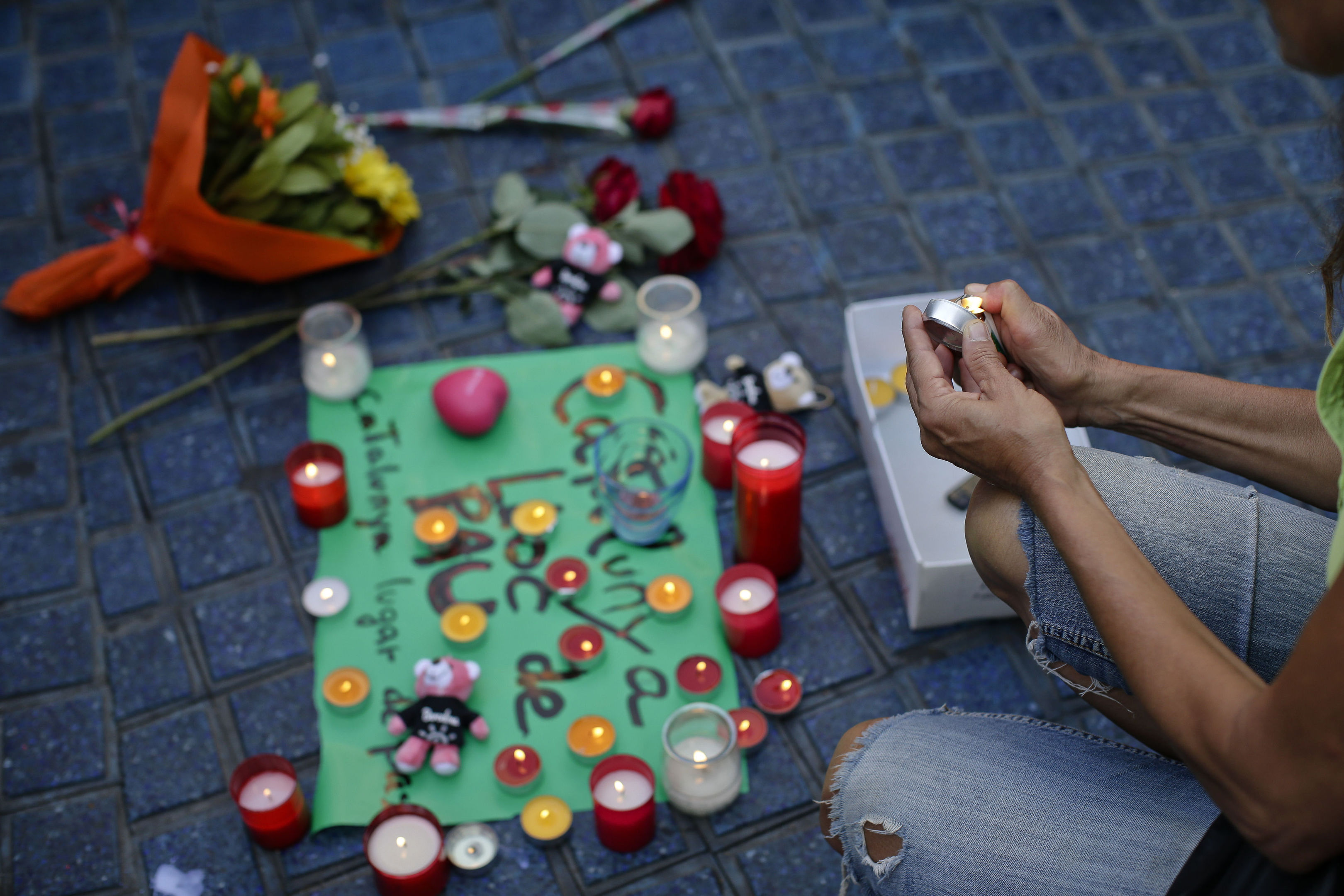 """A woman lights a candle next to a paper that reads """"Catalunya - place of peace"""" in Las Ramblas, Barcelona, Spain"""