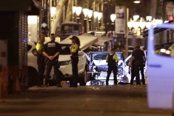 Police officers stand next to the van involved on an attack in La Rablas in Barcelona, Spain