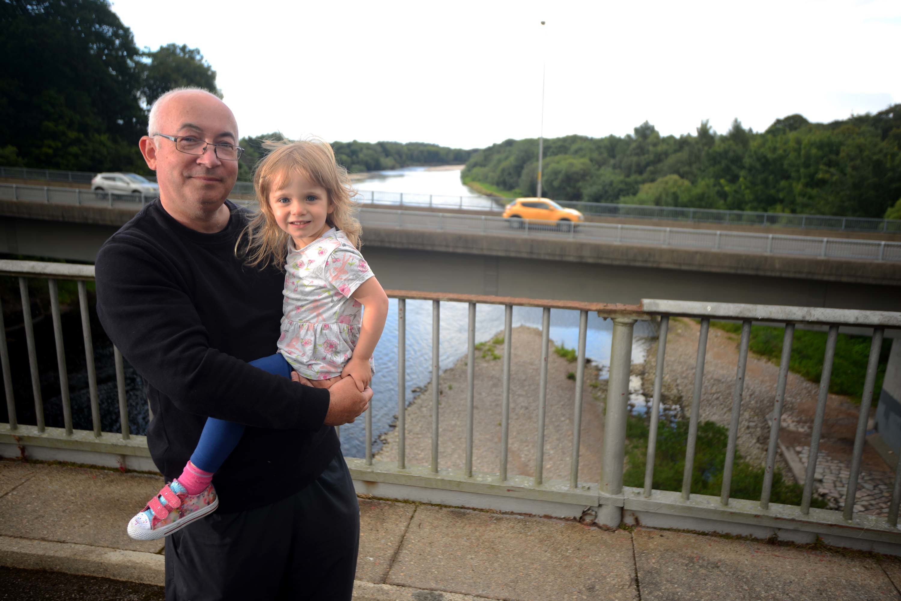 Cllr Marc MacRae at the Old Bridge over the Spey, next to the A96 at Fochabers with his 3 year old granddaughter, Emelia Stanforth.  Photo by Michael Traill 9 South Road Rhynie Huntly AB54 4GA  Contact numbers Mob07739 38 4792 Home01464 861425