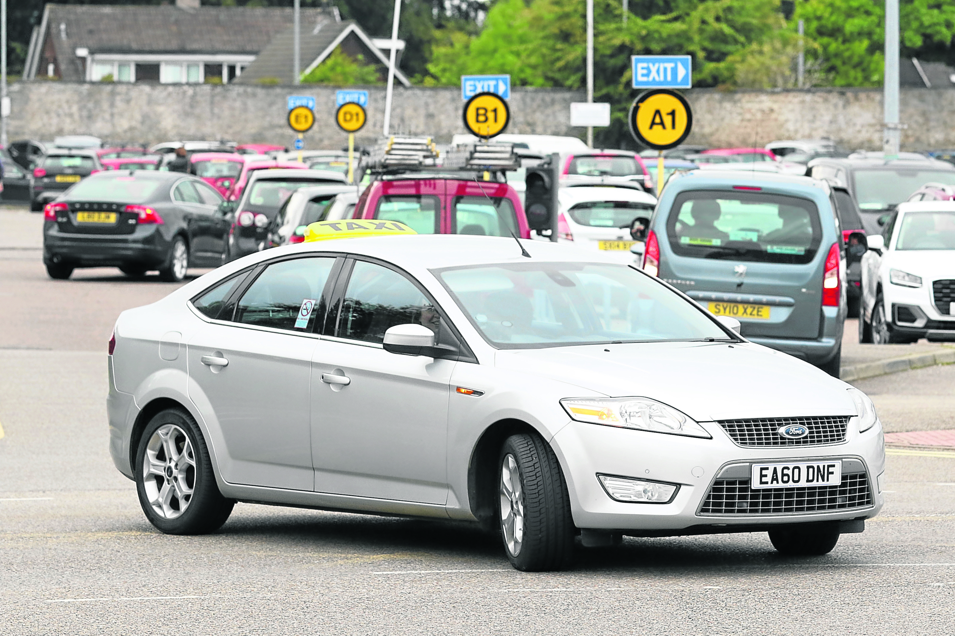 A taxi at Raigmore Hospital with busy car park in the background