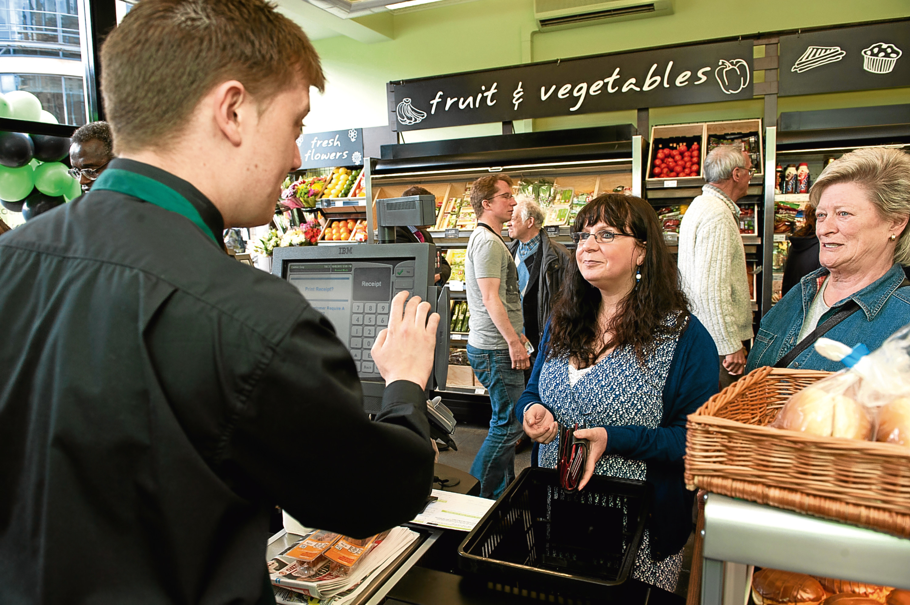 Customers at the till in a Scotmid store