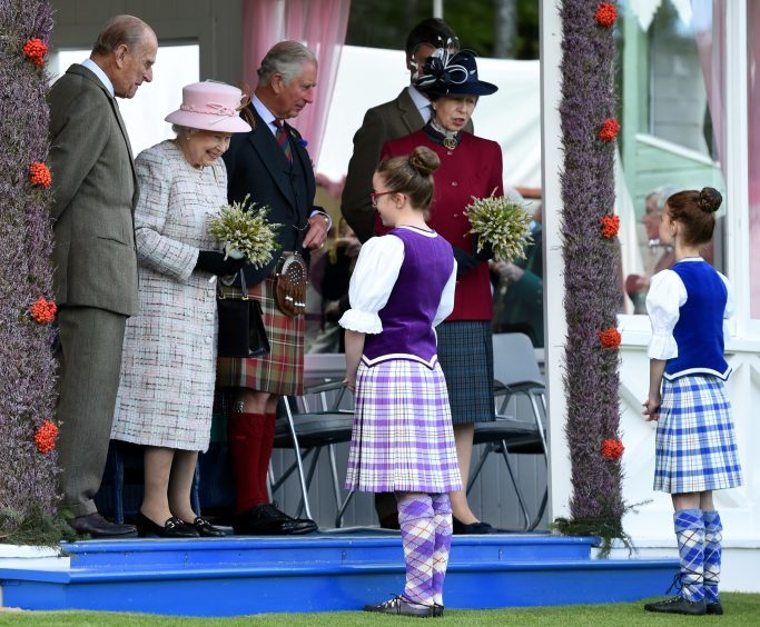 The Queen meets Amy Lawrence and Morgan Strachan, both of Braemar at the games.