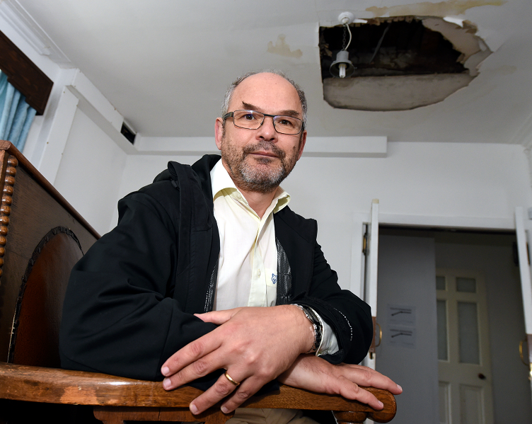 Aberdeen Synagogue president Mark Taylor below the hole caused by the flood