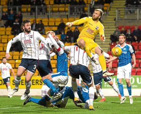 Ross County goalkeeper Scott Fox competes for the ball