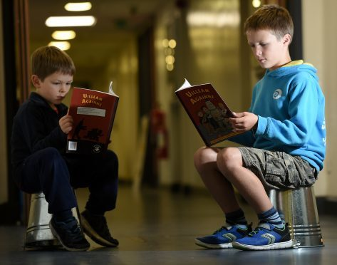 Alasdair Stiubhart enjoys a newly released Oor Willie book which has been translated in to Gaelice and was launched at the Mod. Also in the photograph is younger brother Seumas. Picture by Sandy McCook.
