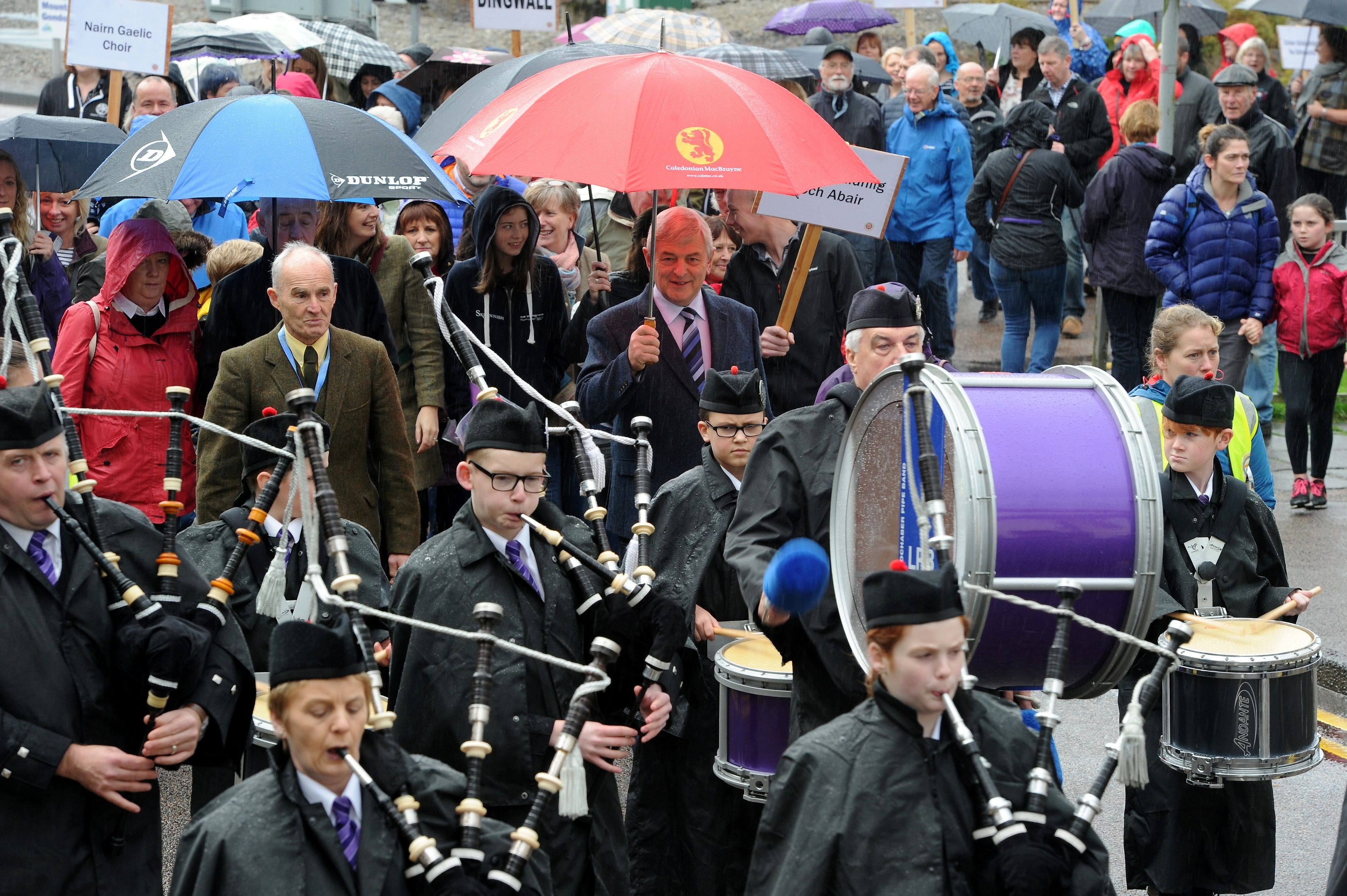 The Massed Choirs are led through Fort William by the Lochaber Pipe Band before performing on The Parade in the centre of the town. Pictures and video by Sandy McCook.