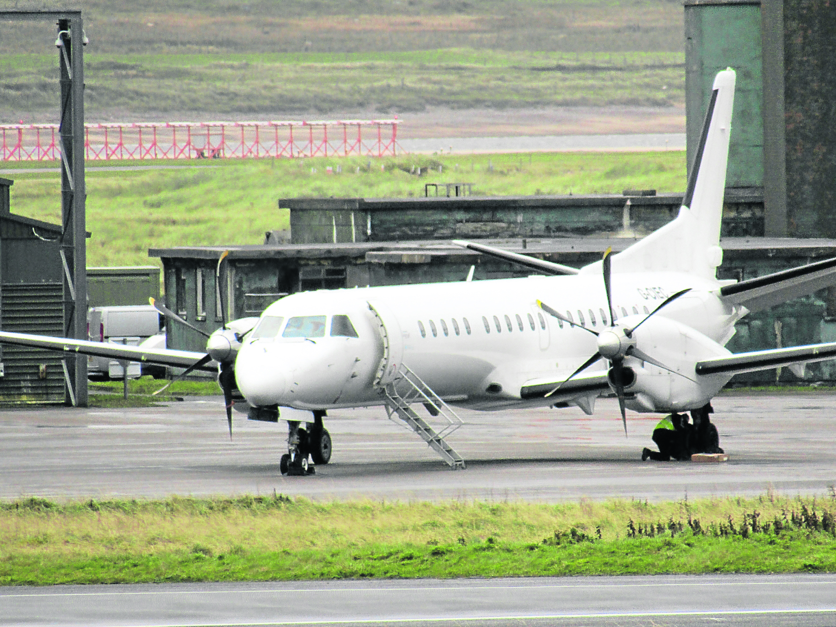 Pis show the wheels of the Saab 2000 being inspected at Stornoway Airport