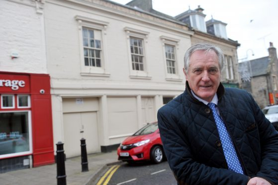Councillor John Cowe in Elgin's High Street in front of the building he wanted to see demolished.
