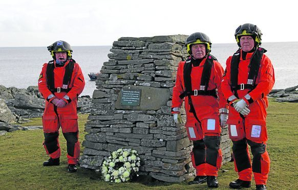 Paying respect at the cairn erected to mark the sad loss of winch man Bill Deacon are (l to r): Terri Mooney, Dave Ellis and Friedie Manson.