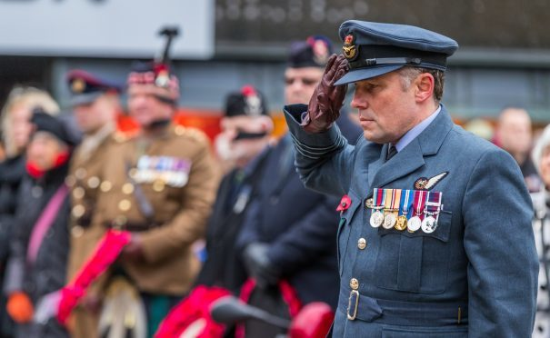 Wing Cmdr David Allen salutes at the Elgin remembrance service.