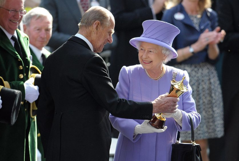 Queen Elizabeth II receives a trophy from the Duke of Edinburgh after her horse Estimate won the Queen's Vase during day four of the 2012 Royal Ascot meeting at Ascot Racecourse, Berkshire. June 2012.