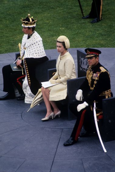 Queen Elizabeth II and the Duke of Edinburgh with the Prince of Wales during his investiture at Caernarfon Castle. July 1969.