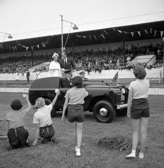 Queen Elizabeth II and the Duke of Edinburgh pass a group of youngsters raising their cups while driving in an open top vehicle around Hove Stadium, East Sussex. July 1962.