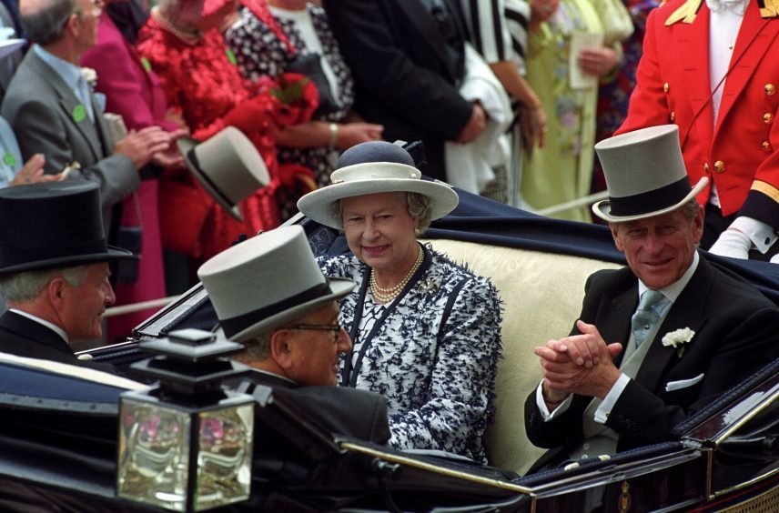 Queen Elizabeth II and the Duke of Edinburgh riding down the course at Ascot. June 1995.