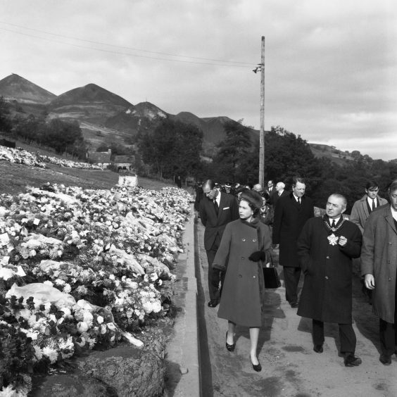 Queen Elizabeth II and the Duke of Edinburgh view flowers during their visit to the village of Aberfan, South Wales, where a coal-tip avalanche killed 144 victims. October 1966.