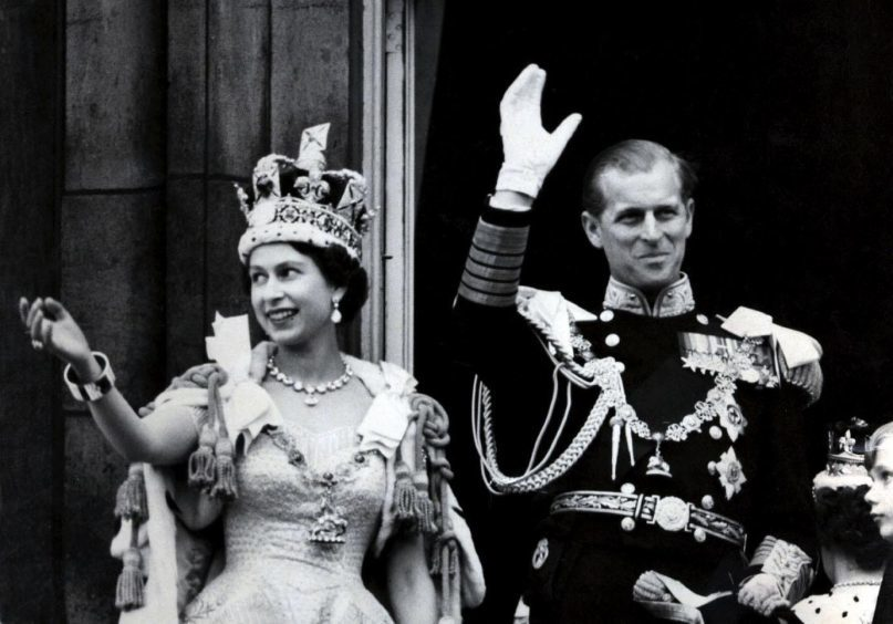 June 1953. Queen Elizabeth II wearing the Imperial State Crown, and the Duke of Edinburgh, in the uniform of Admiral of the Fleet, waving from the balcony of Buckingham Palace after the Queen's Coronation.