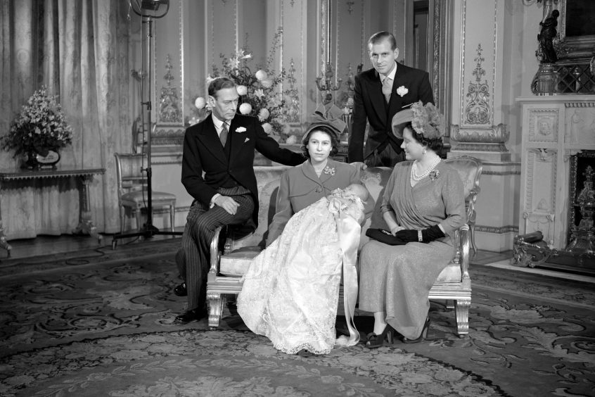 Prince Charles sleeping in the arms of Princess Elizabeth, after his Christening at Buckingham Palace, with King George VI, the Duke of Edinburgh and Queen Elizabeth. December 1948