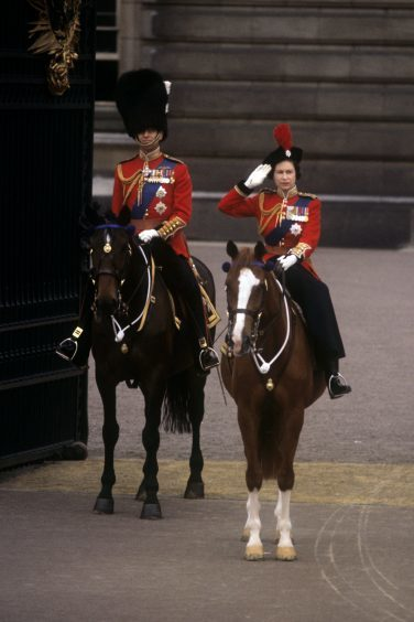 Queen Elizabeth II, accompanied by the Duke of Edinburgh, takes the salute outside Buckingham Palace at the conclusion of the Trooping the Colour ceremony. June 1964.