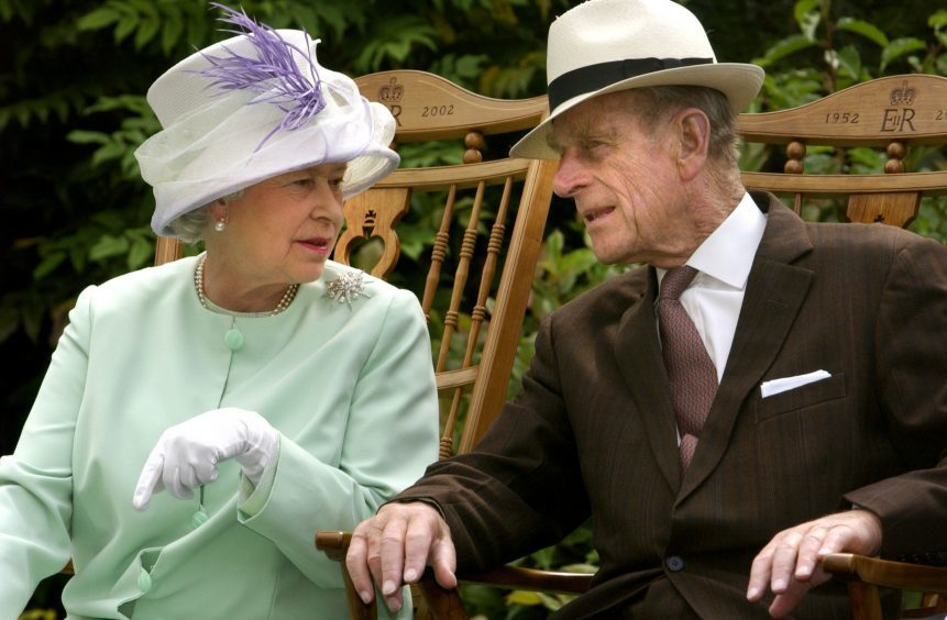 Queen Elizabeth II and the Duke of Edinburgh during a musical performance in the Abbey Gardens, Bury St Edmunds. July 2002.