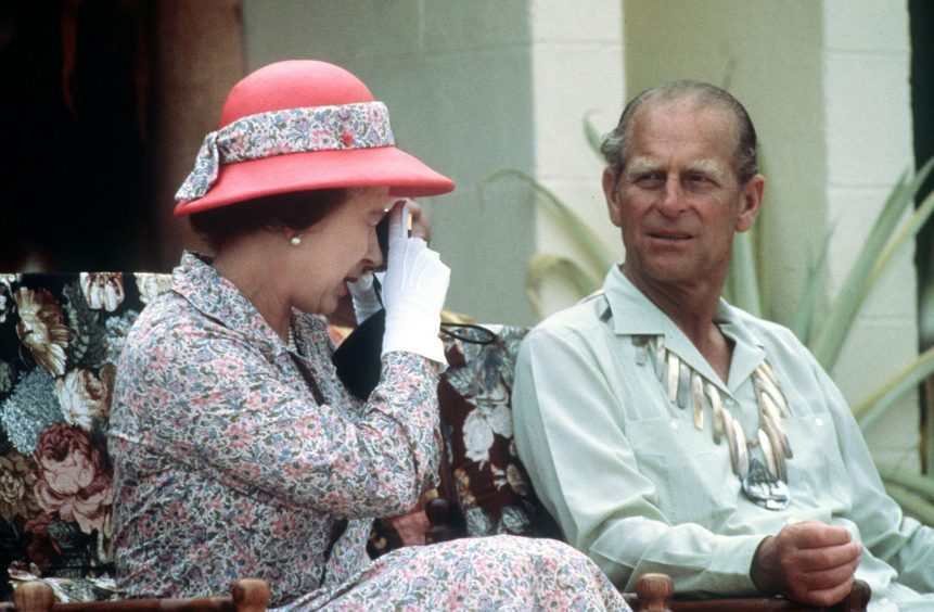 Queen Elizabeth taking a photograph when she and the Duke of Edinburgh visited the South Sea Islands of Tuvalu. October 1982.