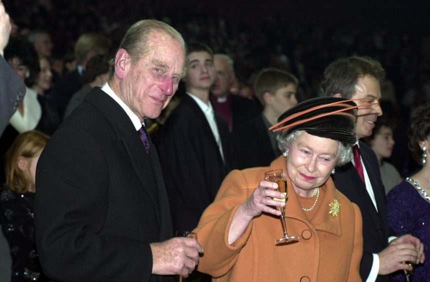 Queen Elizabeth II and the Duke of Edinburgh raising their glasses as midnight strikes during the Opening Celebrations at the Millennium Dome in Greenwich in SE London. January 2000.