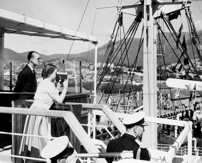 The Duke of Edinburgh watches Queen Elizabeth II as she films the scene at Princes Pier in Hobart, Tasmania. February 1954.