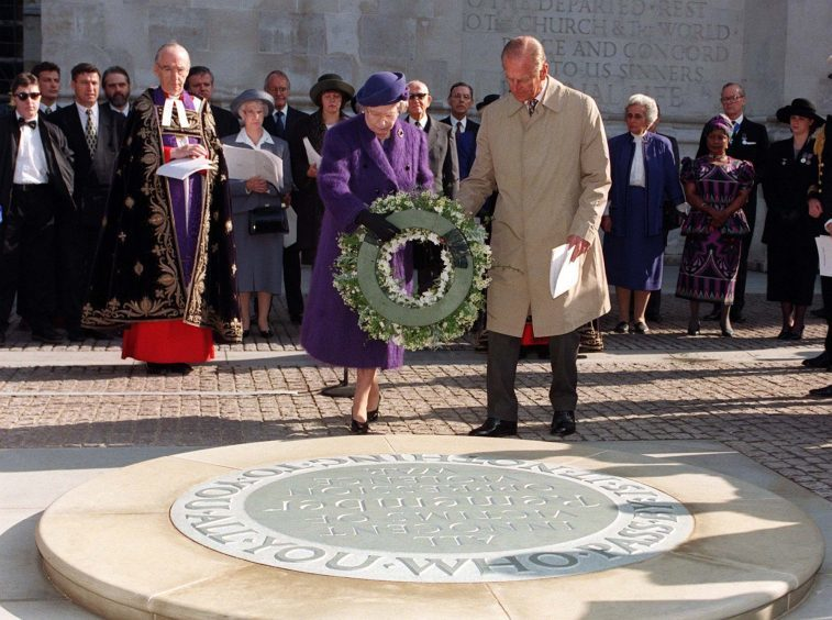 Queen Elizabeth II, accompanied by the Duke of Edinburgh, laying a wreath on the newly-unveiled memorial to all innocent civilian victims across the world, sited near to the Tomb of the Unknown Warrior at Westminster Abbey, during a ceremony. October 1996.