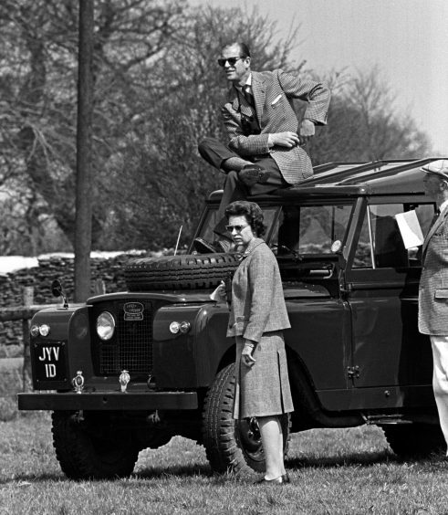 The Duke of Edinburgh perched on the roof of a Land Rover watching the horse trials at Badminton, Gloucestershire, with Queen Elizabeth II. April 1968.