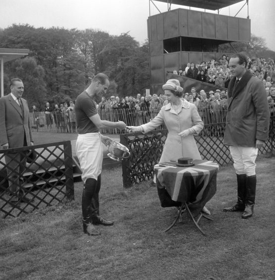 Queen Elizabeth II presents the Royal Windsor Horse Show Cup to the Duke of Edinburgh who, as captain of Windsor Park, had helped defeat Bucket Hill in the final on Smiths Lawn, Windsor Great Park. May 1963.