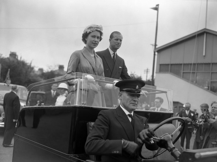 Queen Elizabeth II and the Duke of Edinburgh standing in a Land Rover as they toured Springfield, the showground in Jersey of the Royal Jersery Agricultural and Horticultural Society. July 1957