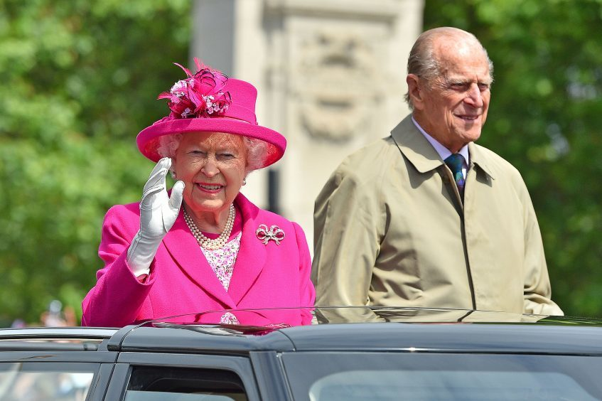 Queen Elizabeth II and the Duke of Edinburgh make their way down The Mall in an open-topped Range Rover, during the Patron's Lunch in central London in honour of the Queen's 90th birthday. June 2016.