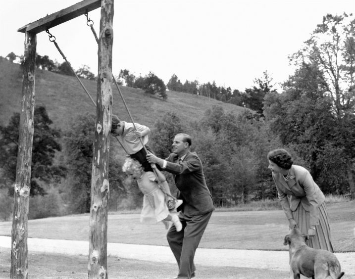 Prince Charles and Princess Anne being pushed on a swing by the Duke of Edinburgh, watched by Queen Elizabeth II, in the grounds of Balmoral. September 1955