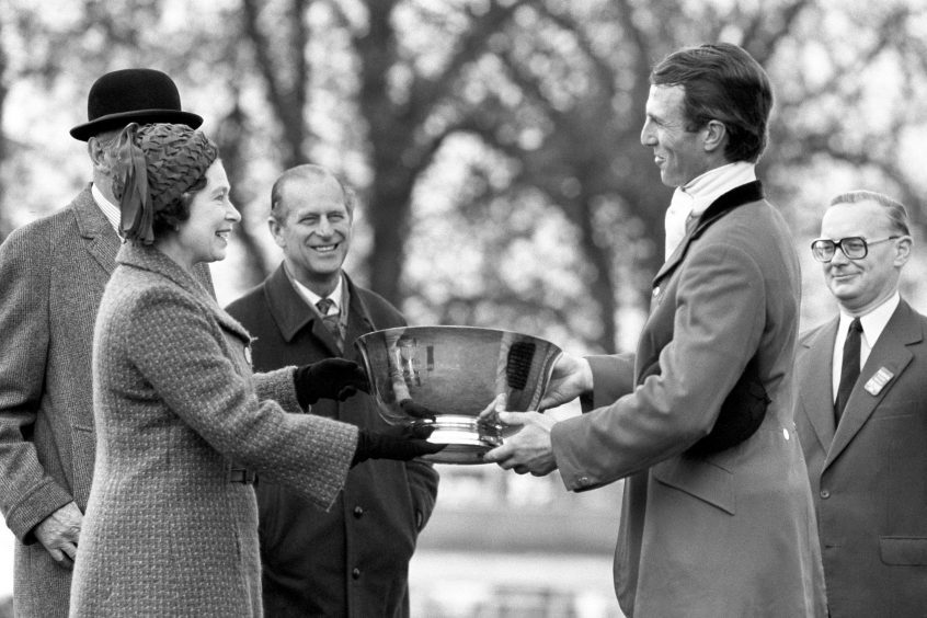 the Duke of Edinburgh watching Queen Elizabeth II and their son-in-law Captain Mark Phillips at the presentation ceremony, after Phillips won the Badminton Horse Trials for the fourth time.  April 1981.